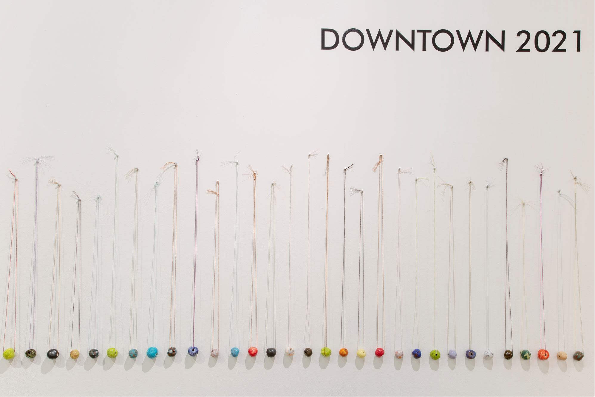 beads hanging on string on a white wall, text above says downtown 2021