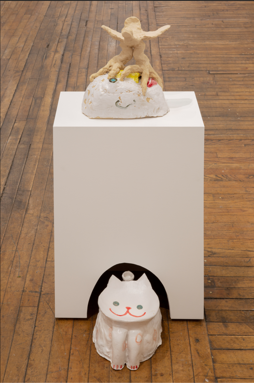 sculpture of a white cat coming out of a white box with a little figure on top