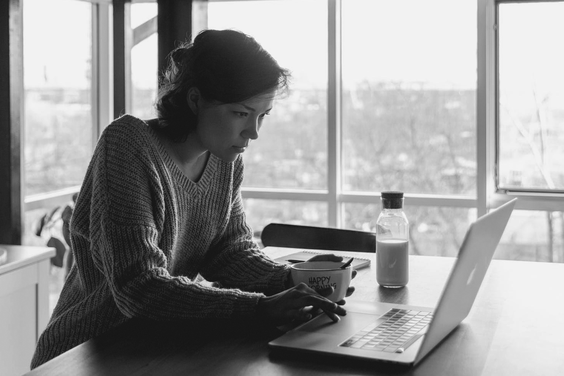 A young lady using a laptop with a cup of tea next to her
