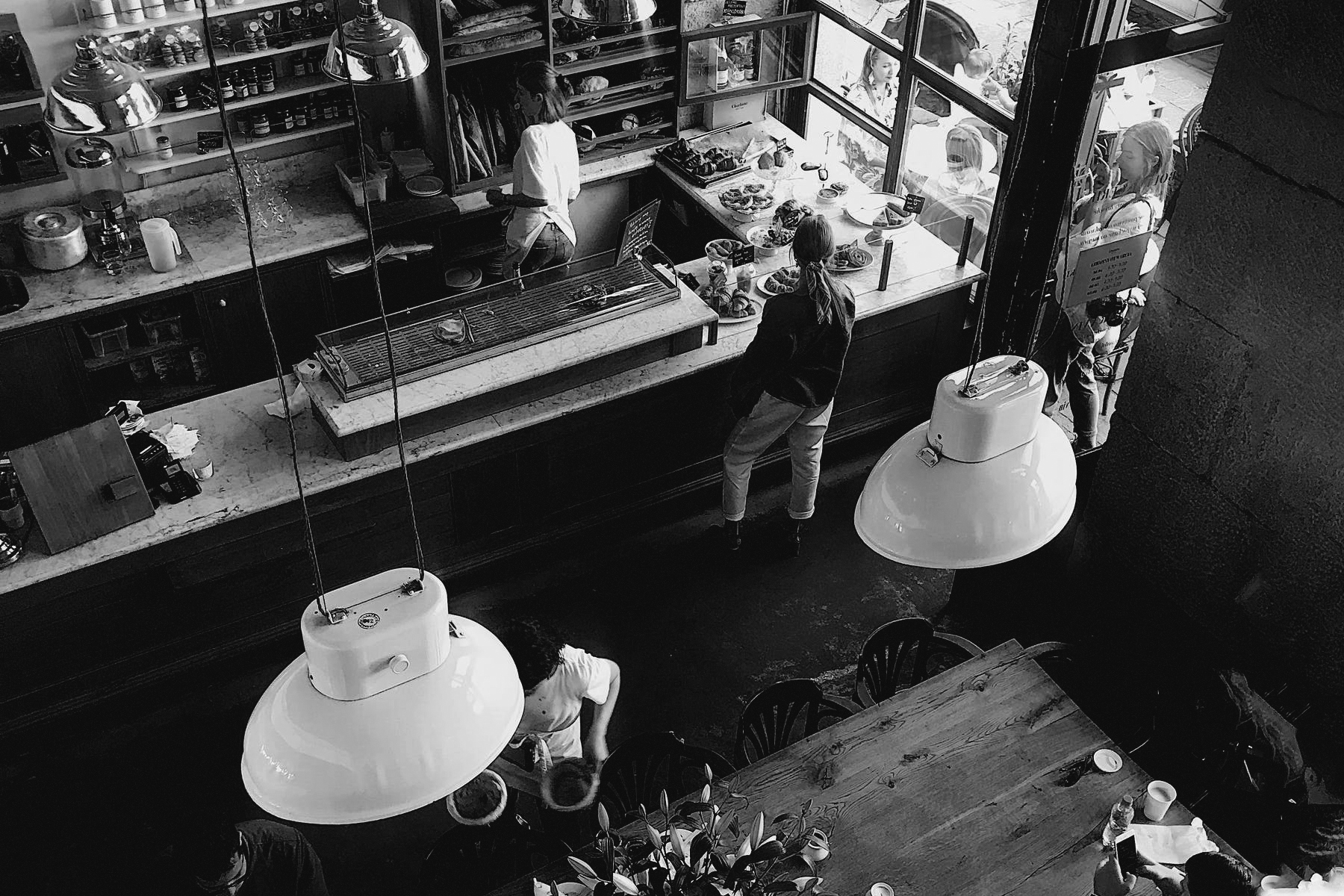 A cafe with people inside drinking coffee and a working serviing customers