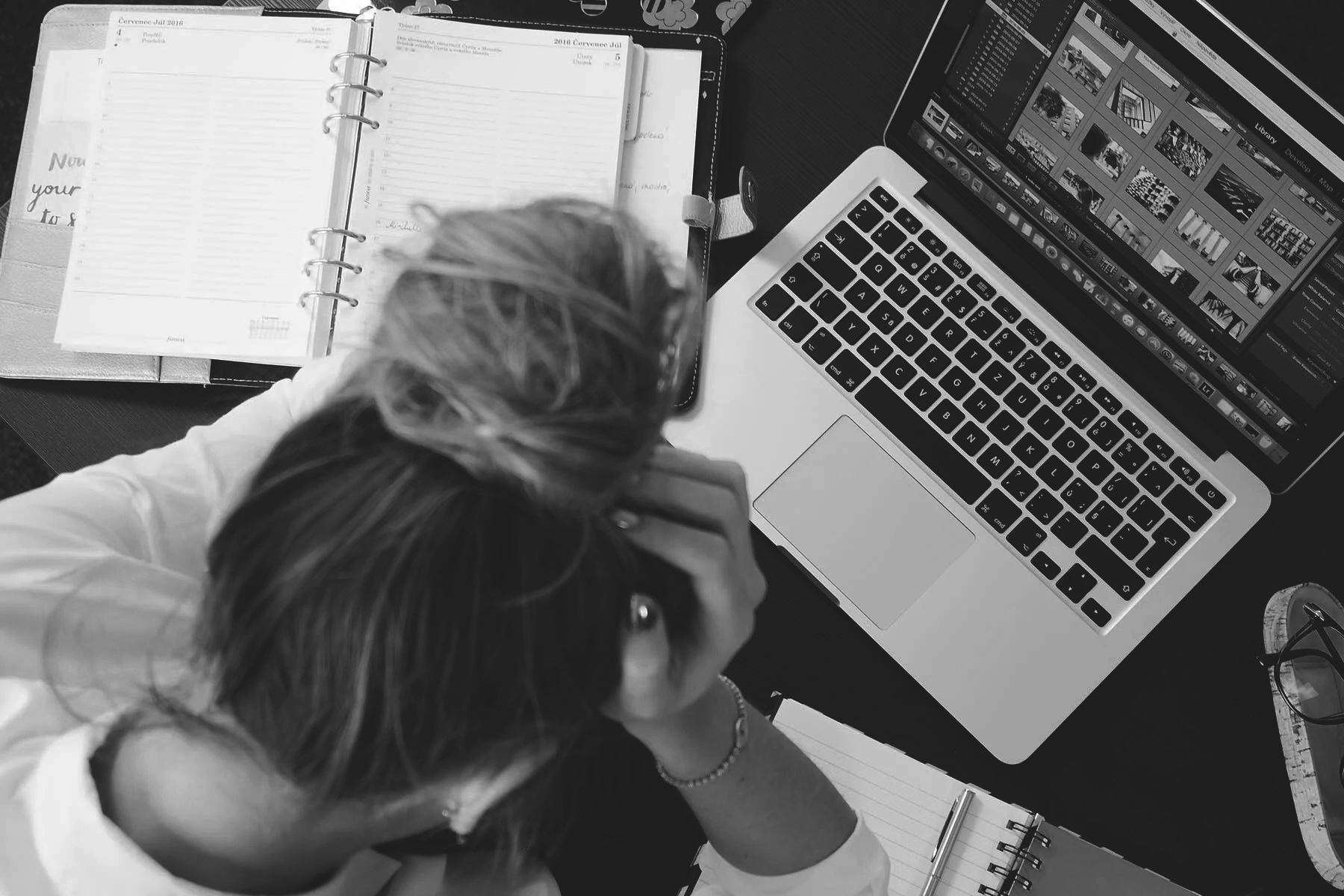 A young woman infront of  a laptop and books frustrated with her head in her hands