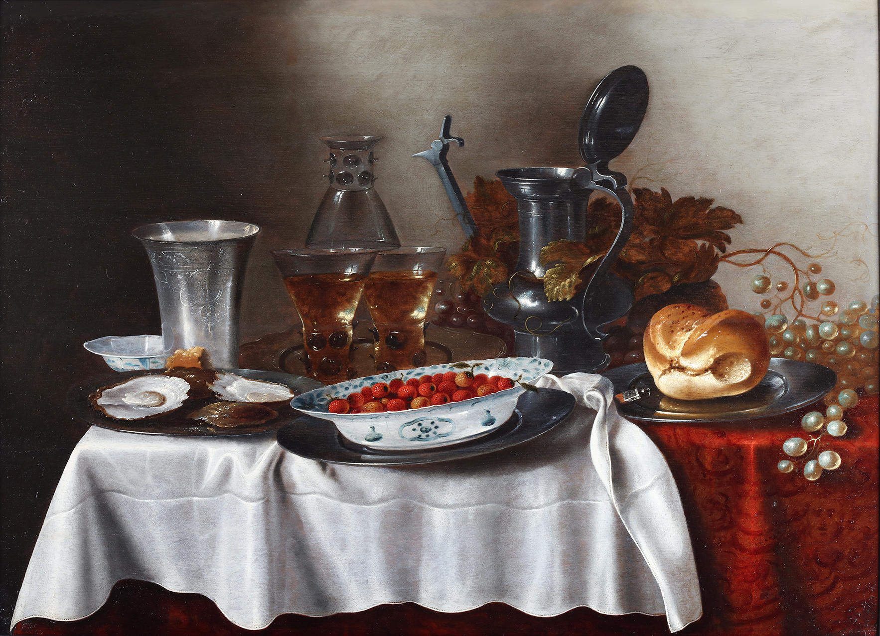 A still-life of a silver cup, strawberries in  wan-li bowl, a loaf of bread and three roemers on a table ledge decorated with a red table cloth