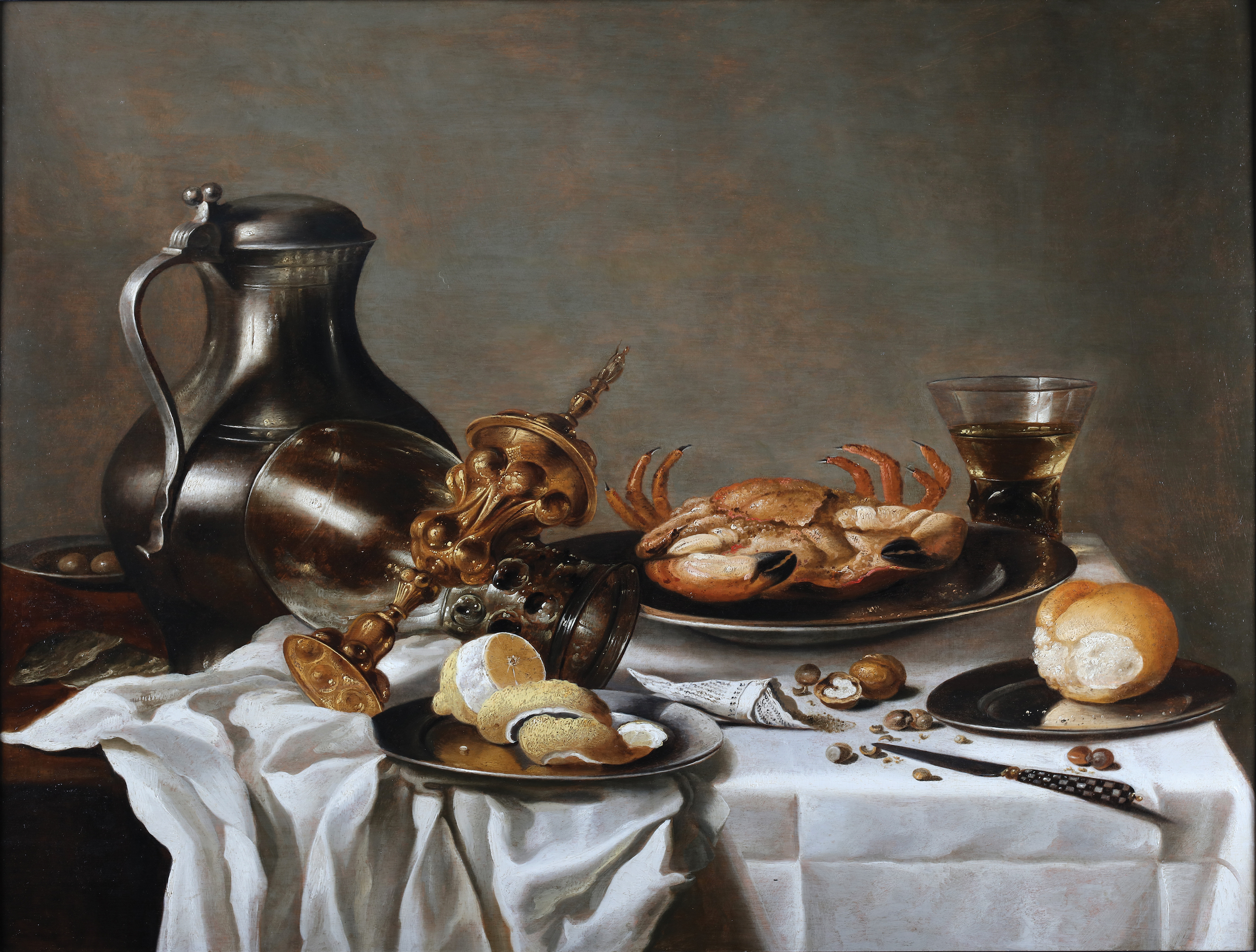 Still life with a peeled lemon, a pewter to the left, a roemer, a bread, a crab, a wine glass and a columbine cup on a table with a white wrinkled table cloth.