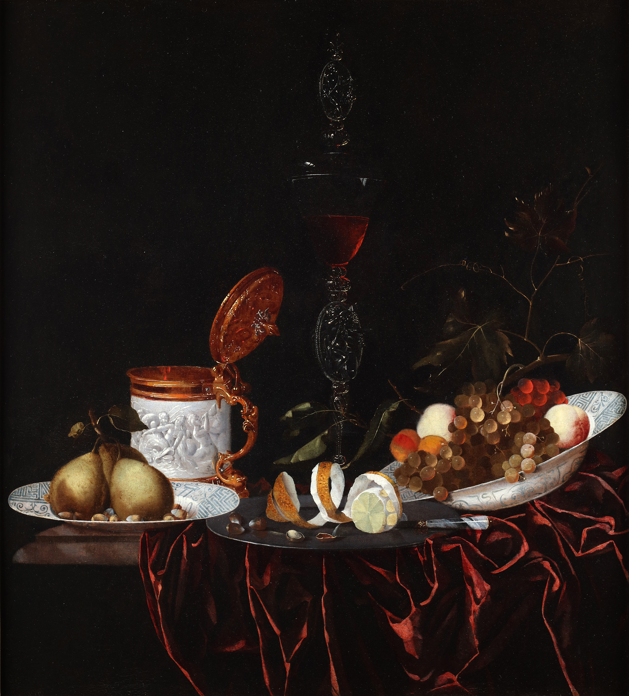 Still life with two Wanli dishes with grapes, pears and other fruits, a peeled lemon and nutshells on a tin plate and a crystal wine glass with the representation of Bacchus