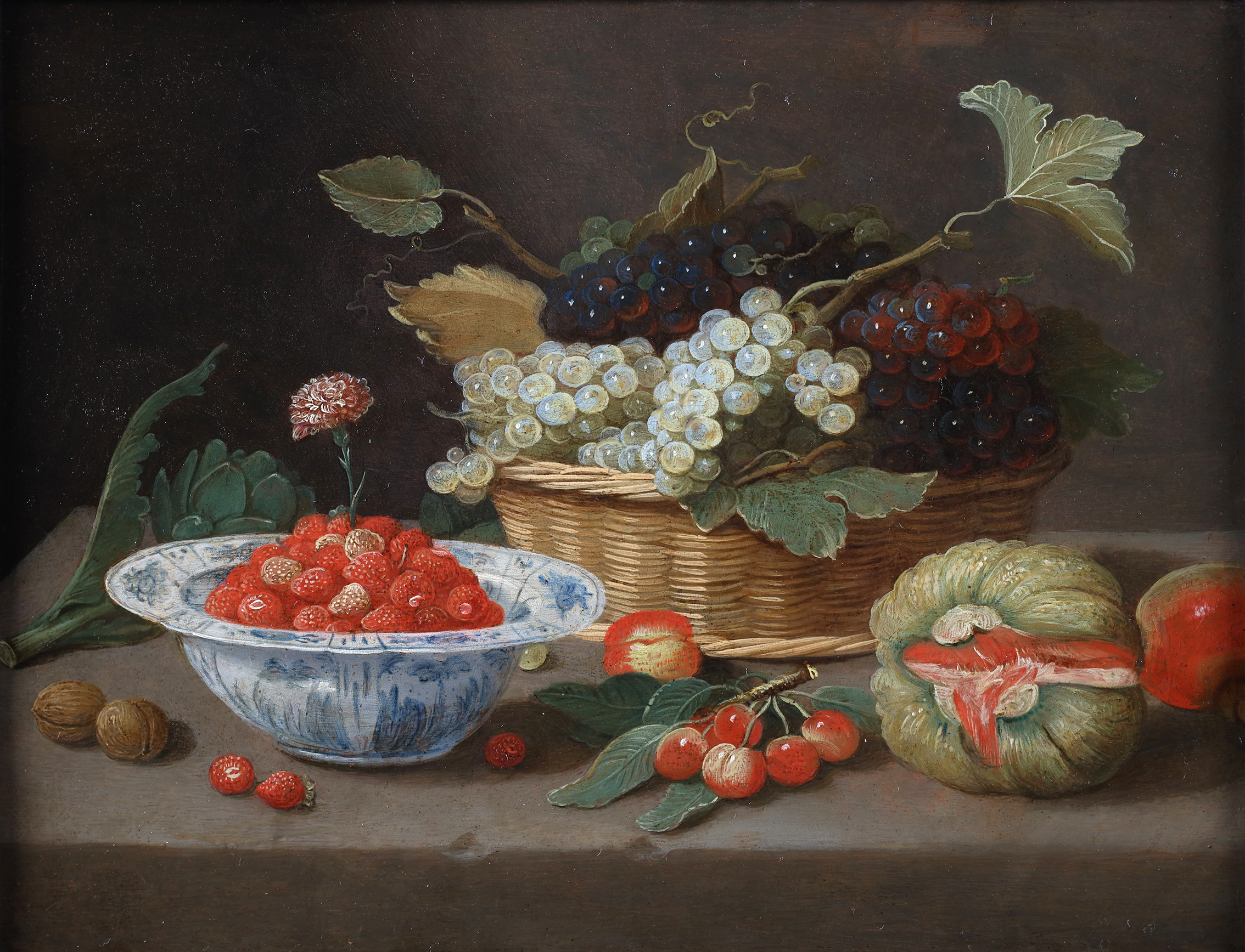 A basket with grapes, a Wanli bowl with strawberries, some cherries and a melon