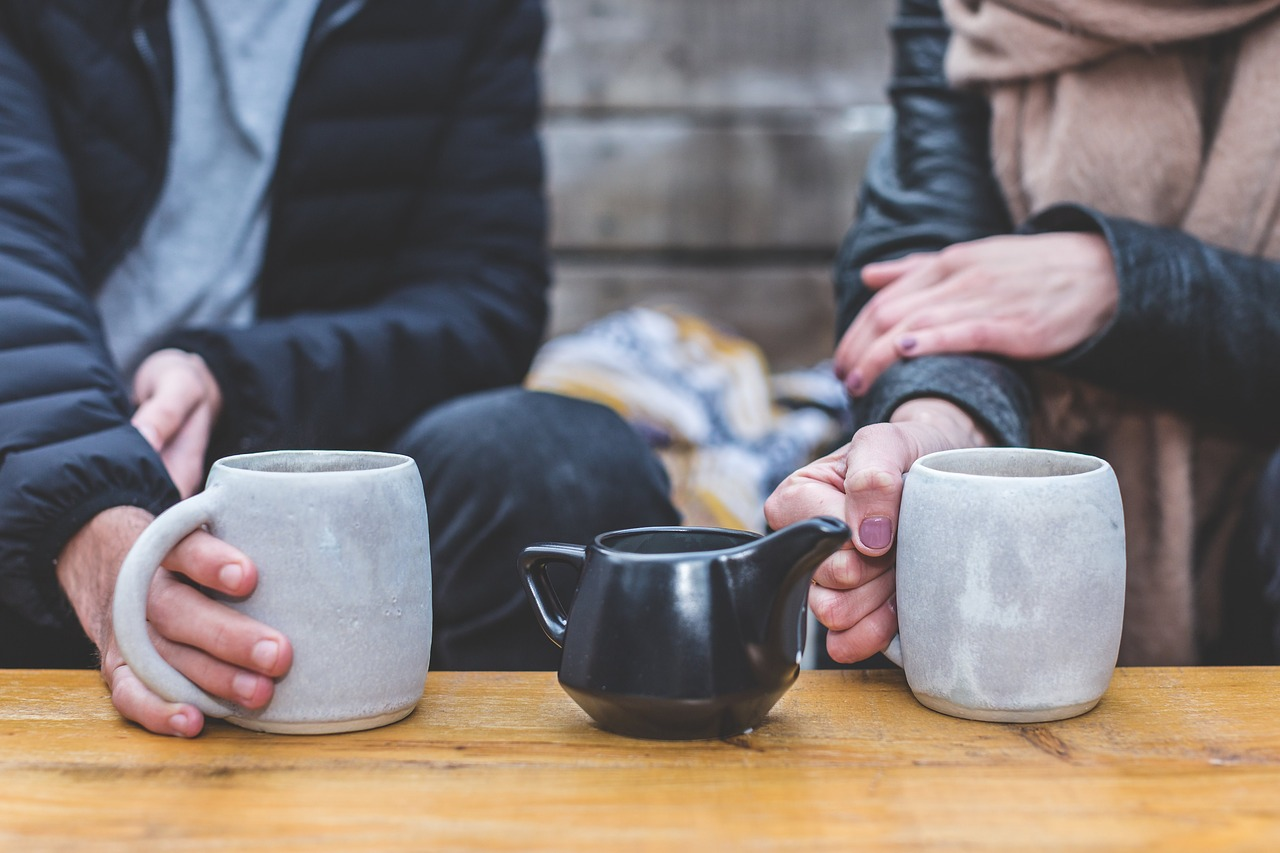 Man and woman holding coffee cups with a tea pot in the middle
