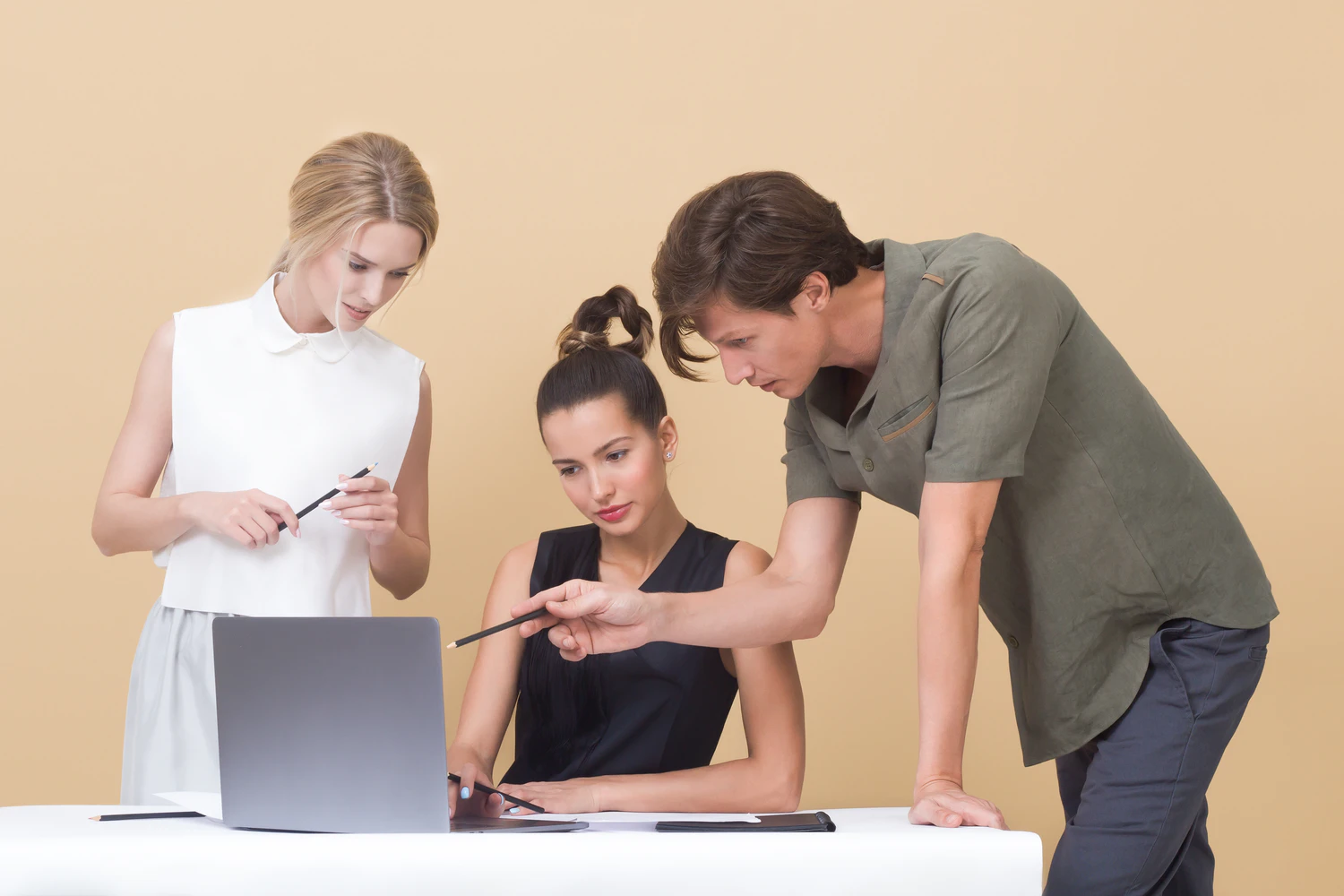 Three people in front of a beige background, looking over the same laptop
