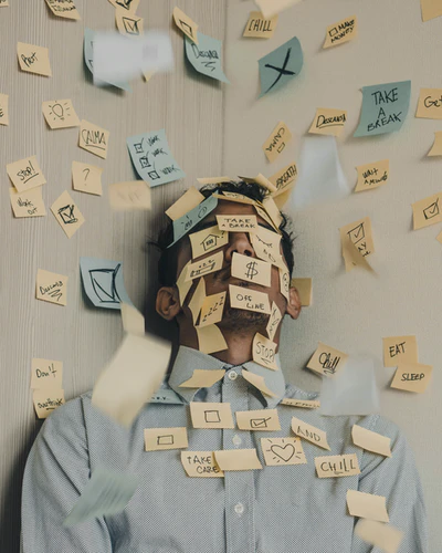Man covered in yellow and blue sticky notes, looking stressed
