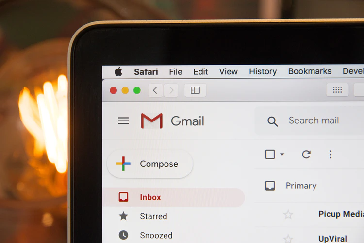 Corner of a Macbook laptop, showing Gmail open on Safari