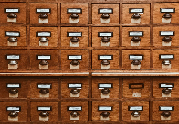 Rectangular wooden file cabinets lined up in rows and columns