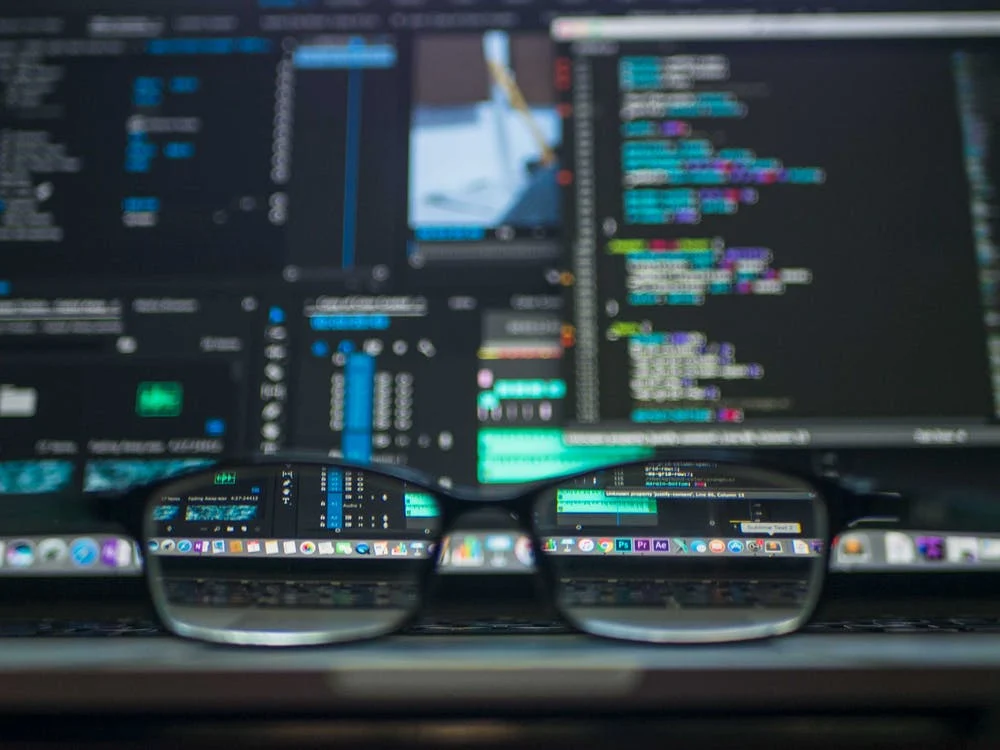 glasses sitting in front of a computer monitor with blurred out windows of data and code