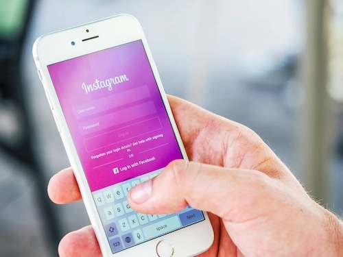 person holding white iphone displaying a pink instagram login