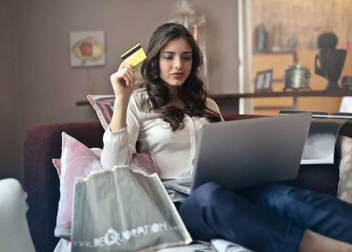 women on her laptop holding up a yellow credit card