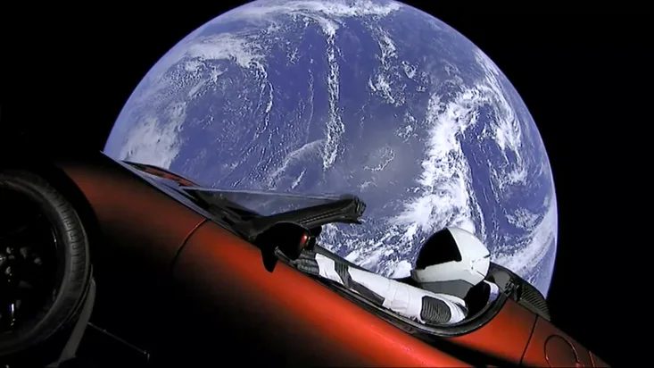Tesla Roadster car with a mannequin astronaut floating in space.