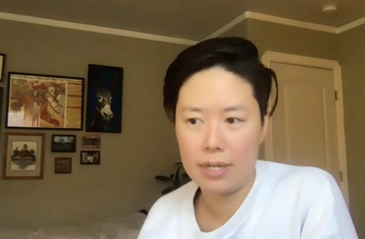 A photograph of a person with short black hair and a white sweatshirt in the middle of speaking. The quality of the photo is grainy due to it being a screenshot of a video