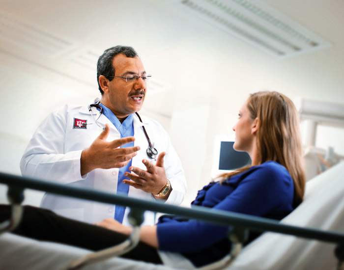 Doctor talking to a patient on a hospital bed