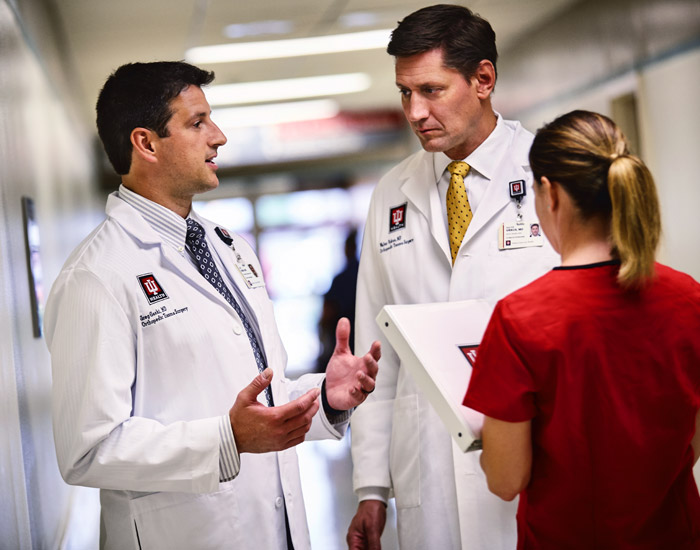 Two doctors and one nurse talking to each in the hallway of a hospital.