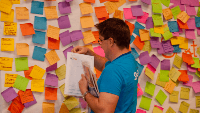 Man standing at post-it note wall