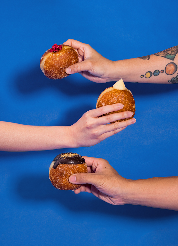 Three hands holding Bakehouse doughnuts