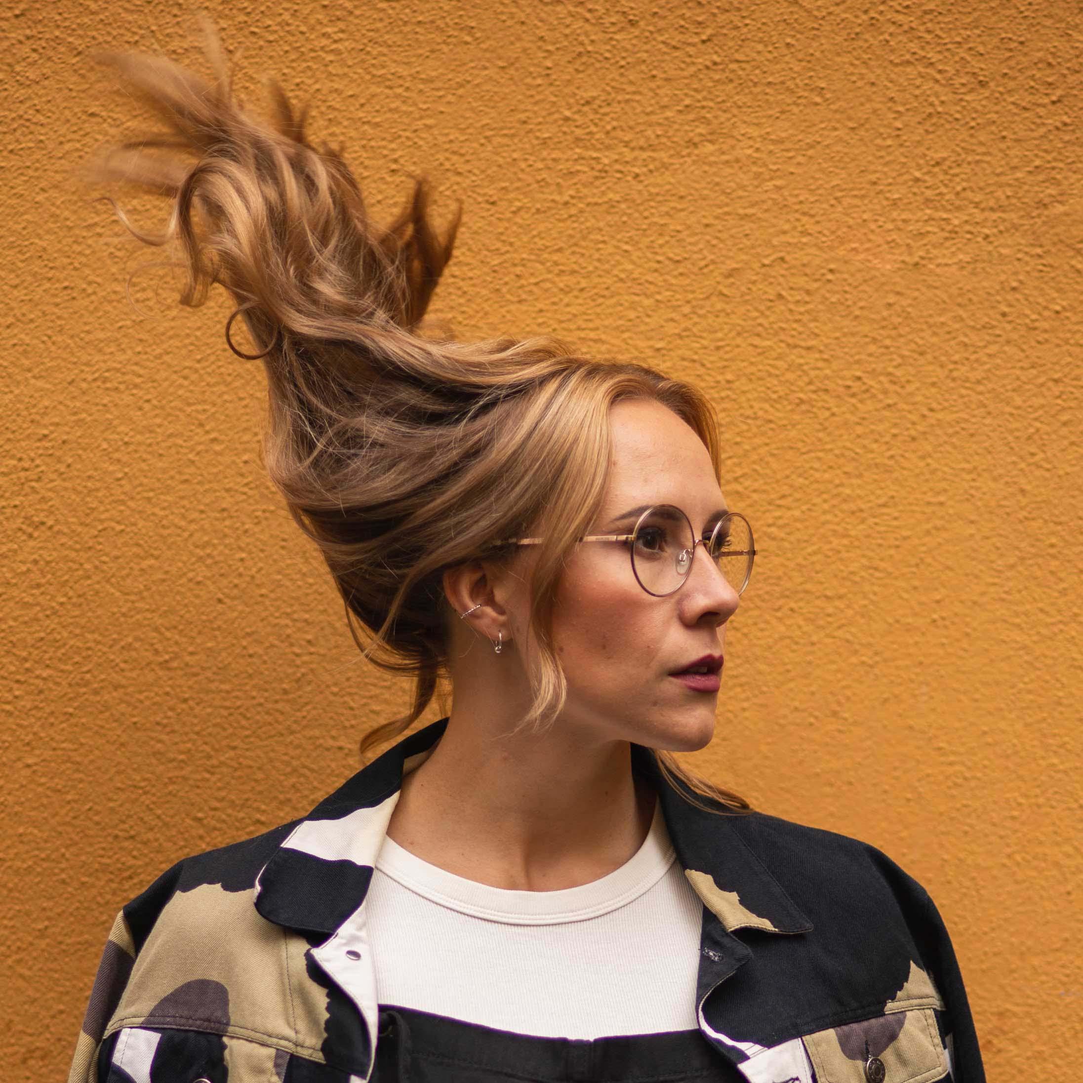 Nainen, jonka pitkät hiukset hulmuavat tuulessa.