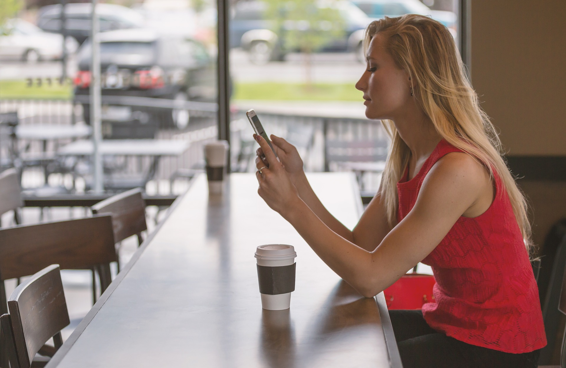 Woman sitting at wooden table with coffee watching video on phone