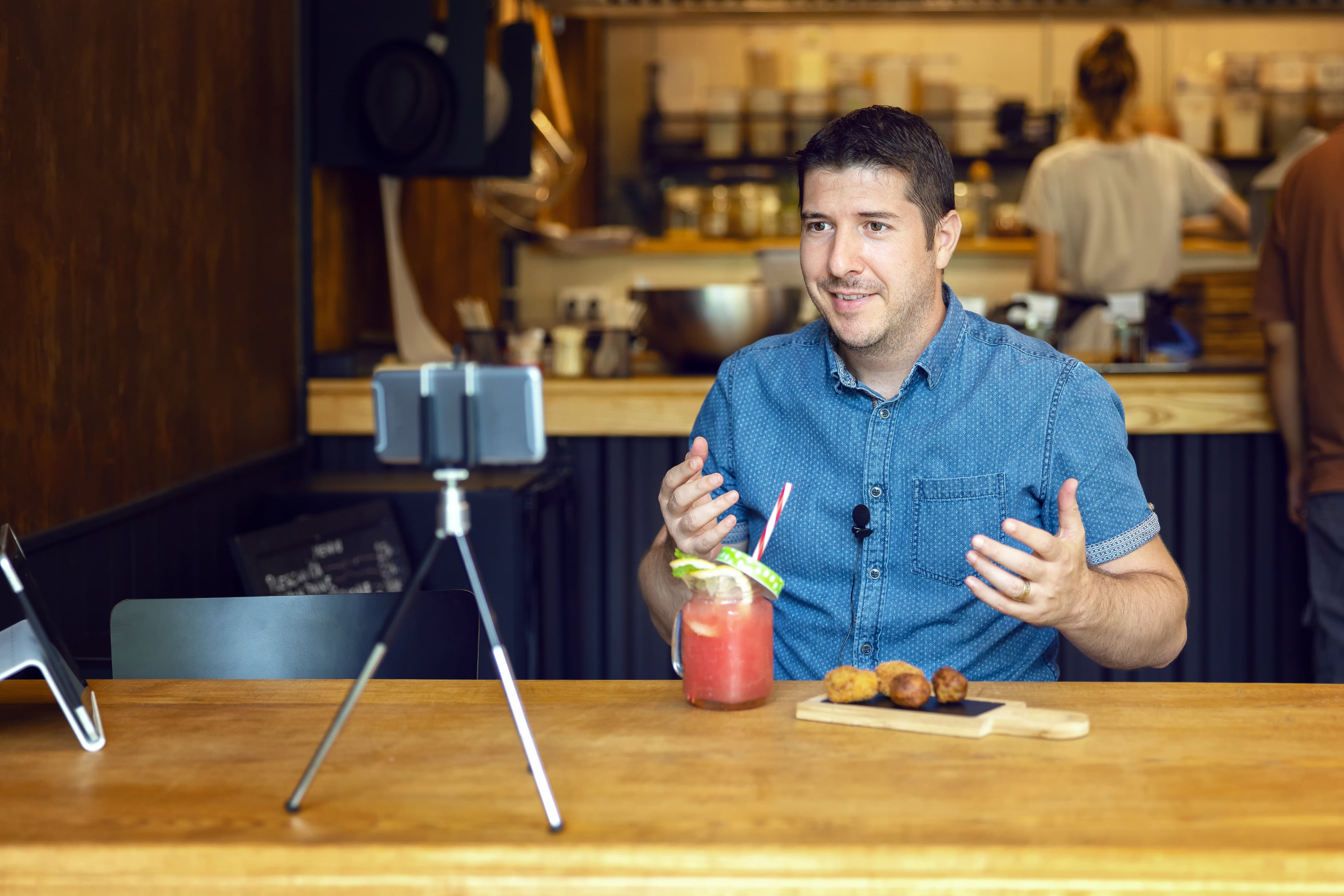 Man sitting at wooden table speaking into phone on a tripod and eating donuts.