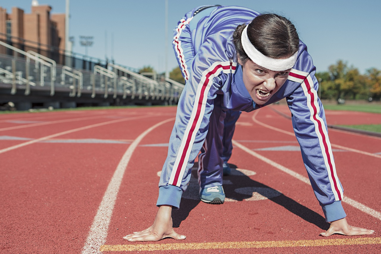 Grunting woman in tracksuit getting ready to sprint across track