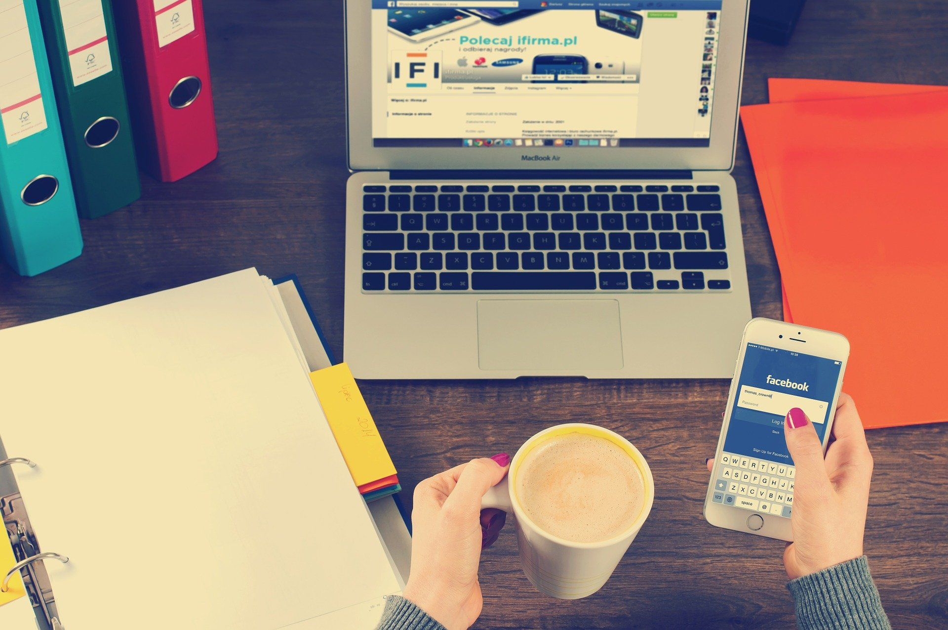 Woman holding phone and coffee sitting at desk with folders and laptop.