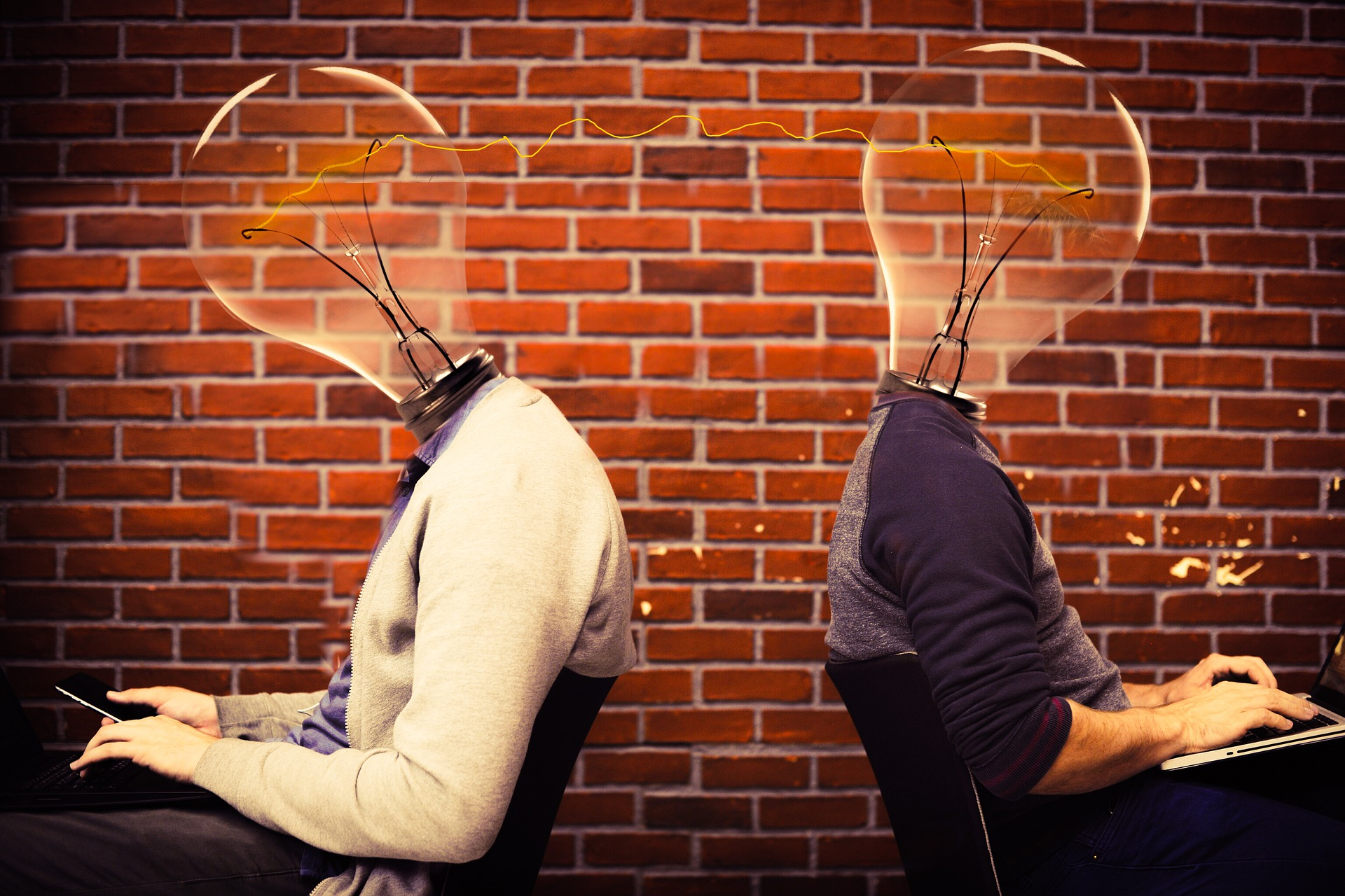 Two men with lightbulb heads sitting down facing away from each other.
