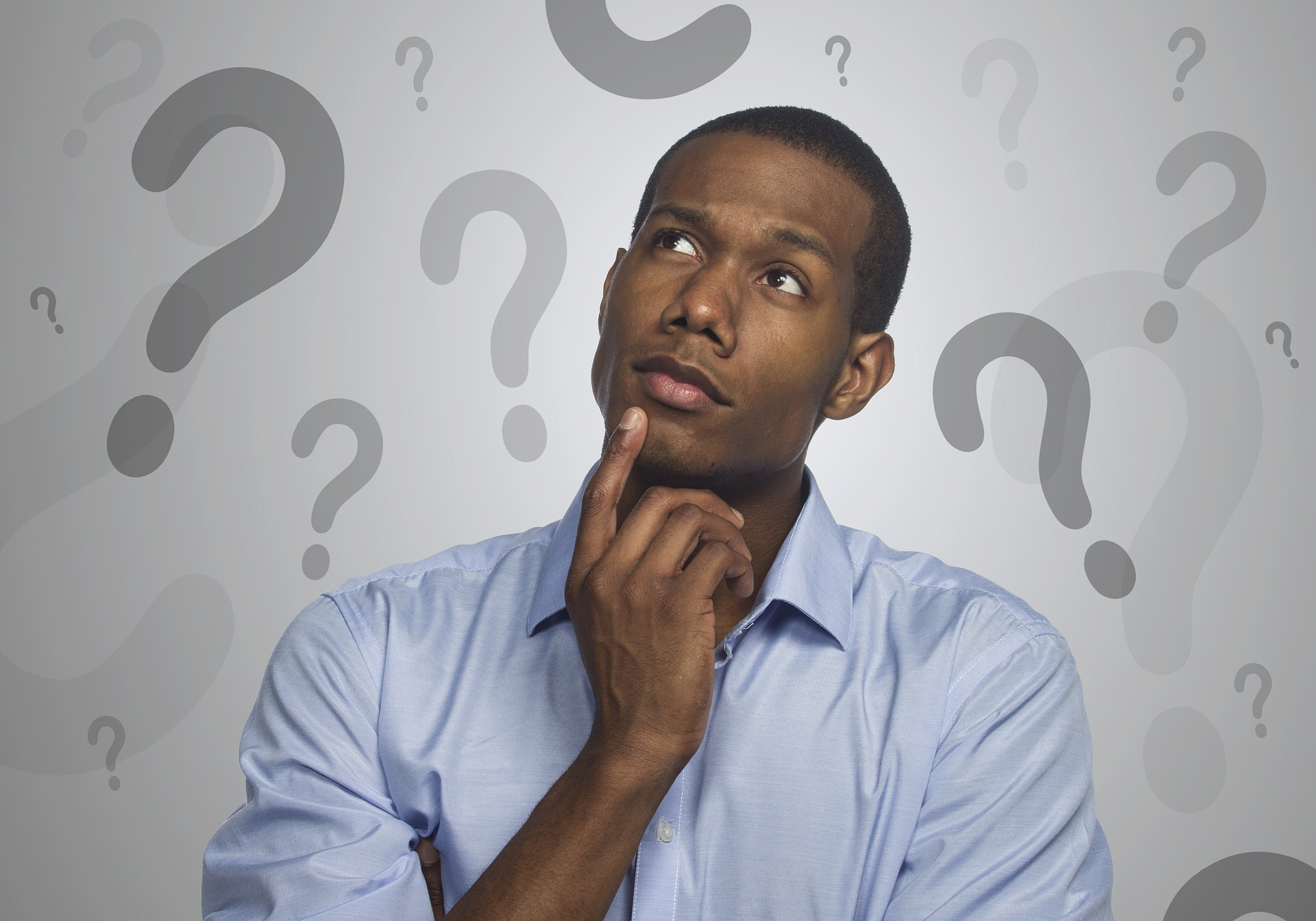 Man pondering with hand on chin with question marks floating around him