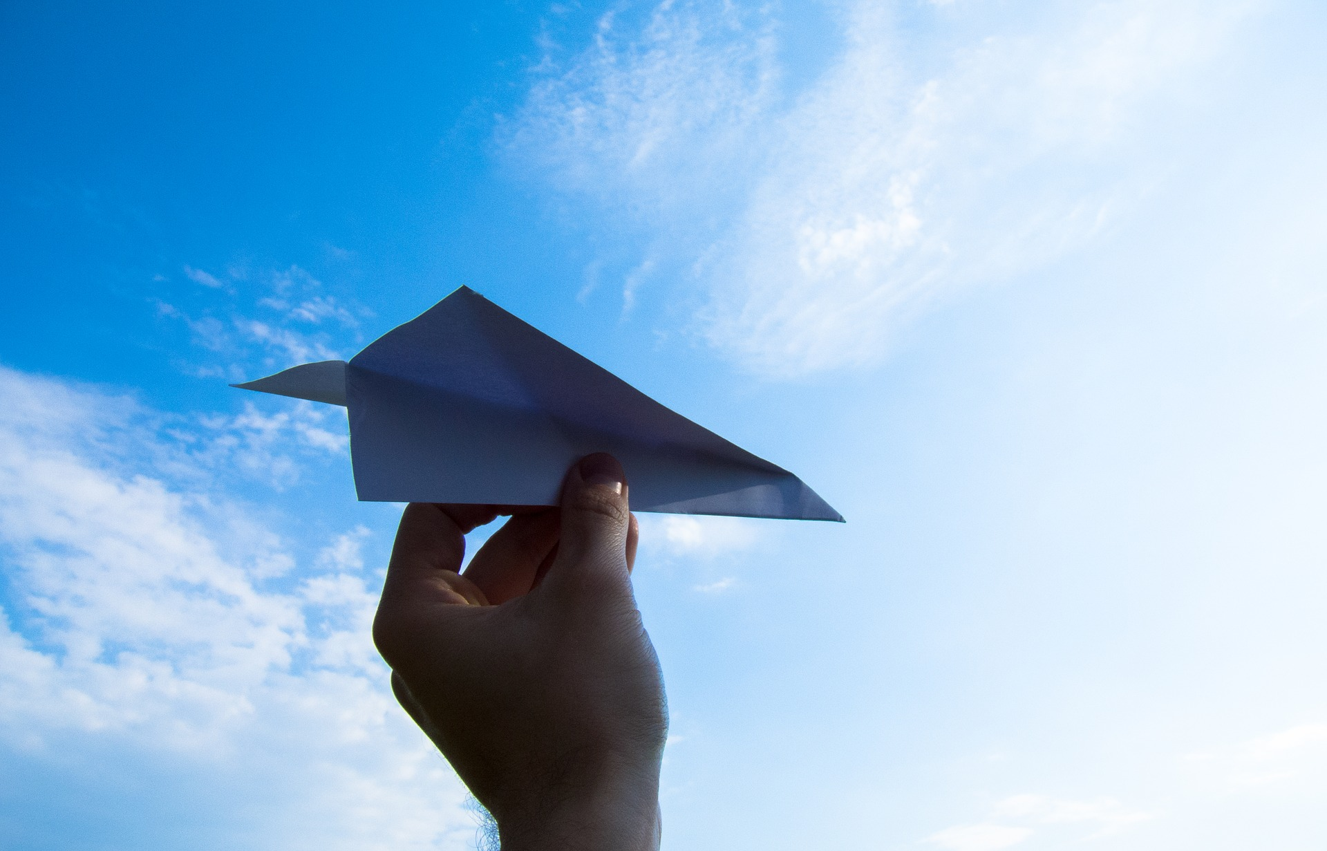 Hand holding paper plane up to a blue sky.