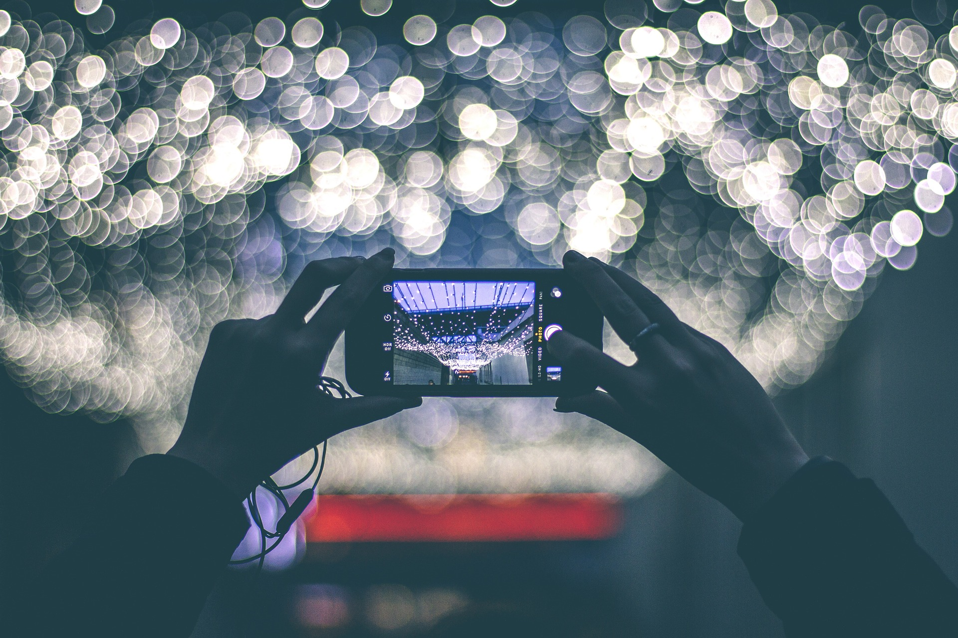 Hands holding phone horizontally facing array of fairy lights at night
