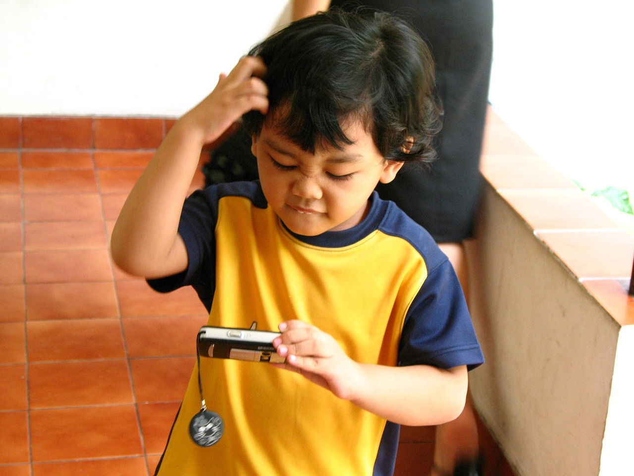 Puzzled toddler looking at phone in hand and scratching head