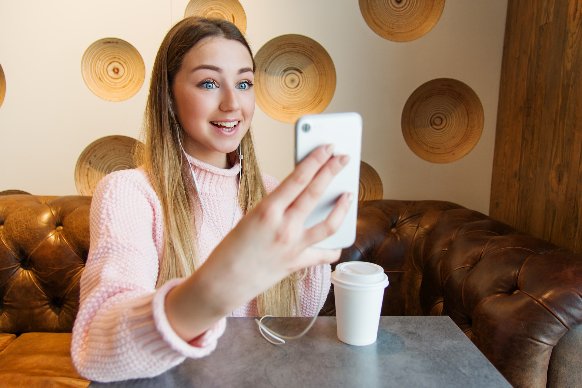 Girl sitting at table in cafe recording video message on phone.