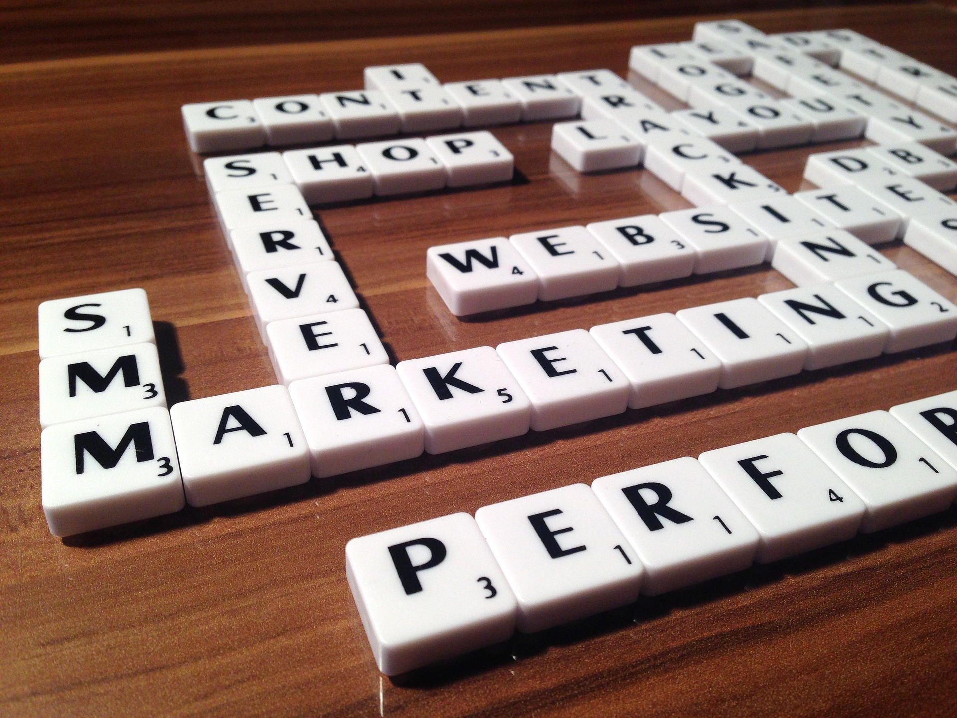 White scrabble pieces on wooden floor arranged into words