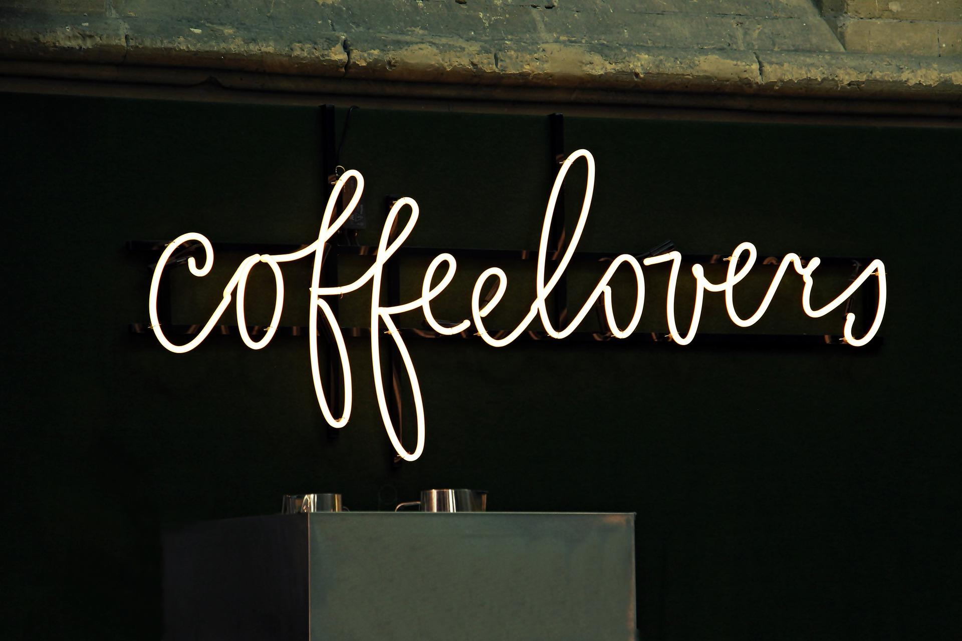 """Brown neon """"Coffee Lovers"""" sign against dark oak wall."""