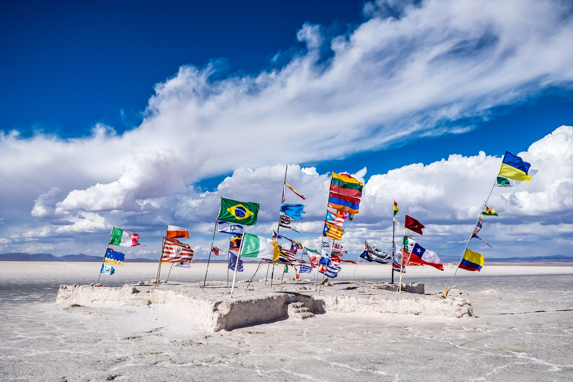 South American flags sticking out of beach on a summer's day with a blue sky.