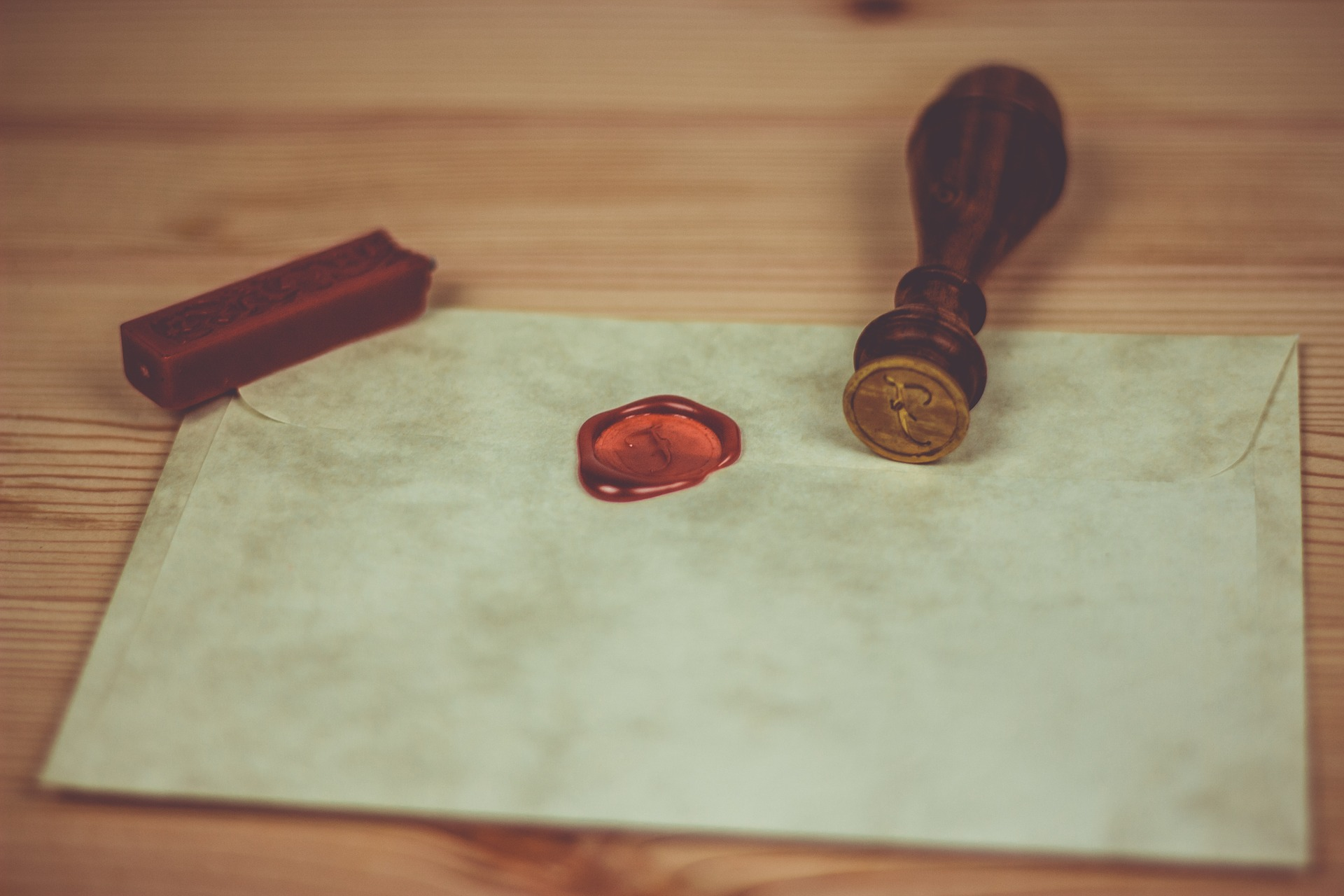 Letter lying on a wooden table with a red wax stamp pressed into the centre.
