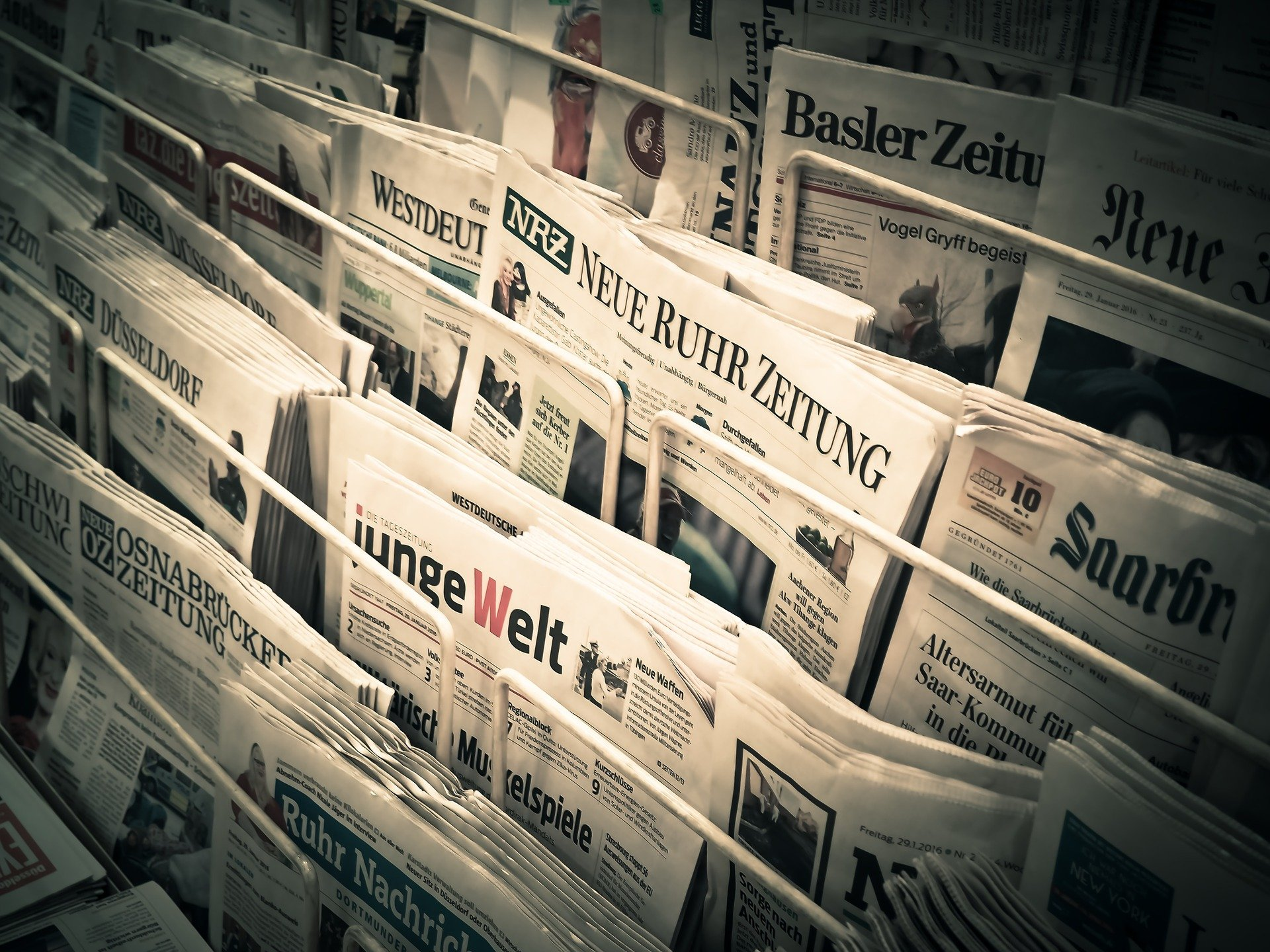 Array of newspapers lying on newspaper stand.