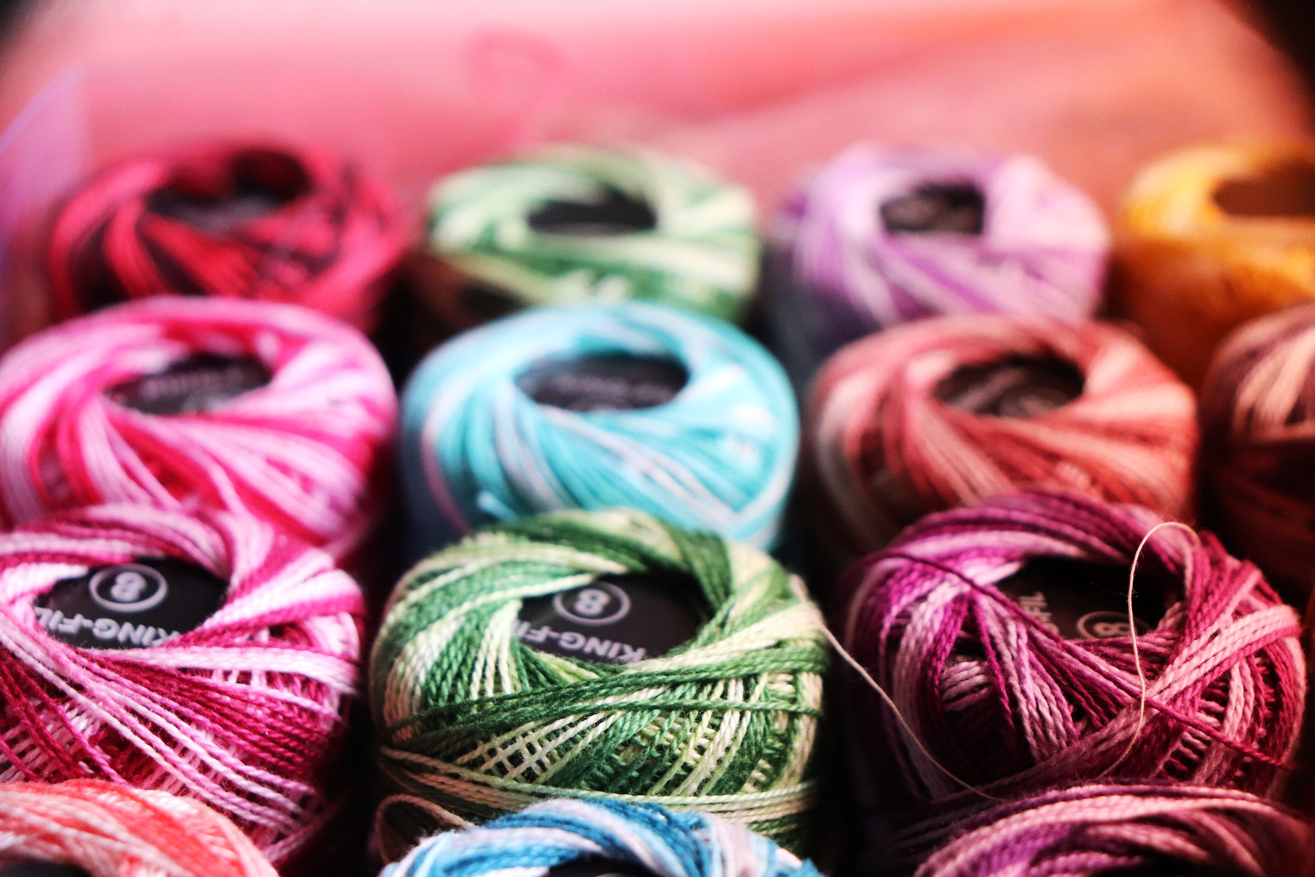 Array of colourful green and pink thread.