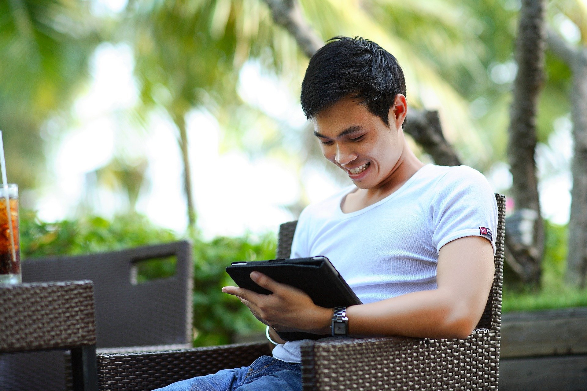 Man sitting on outside deck chair smiling and tapping on iPad.