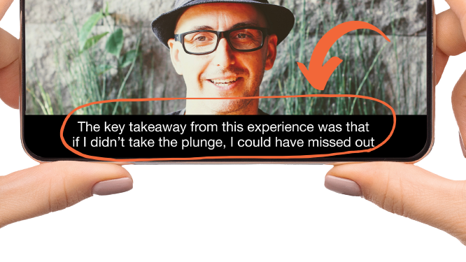 Two hands holding phone horizontally. Phone screen shows man wearing fedora and glasses speaking to camera with captions underneath him.