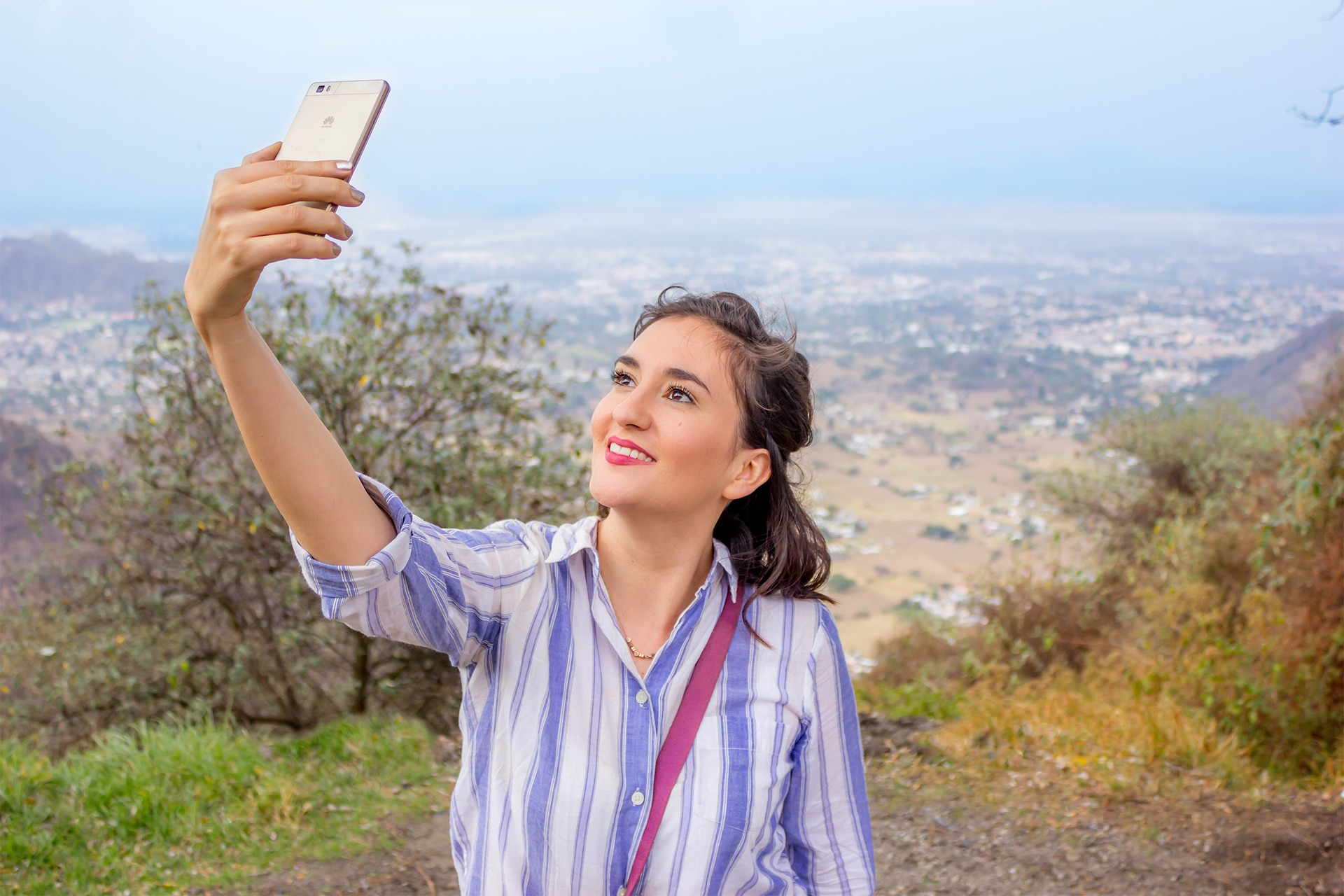 Woman smiling on hill in summer recording selfie video on phone