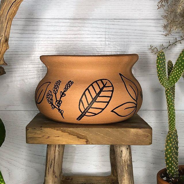 Terra cotta pot with botanical decoration.