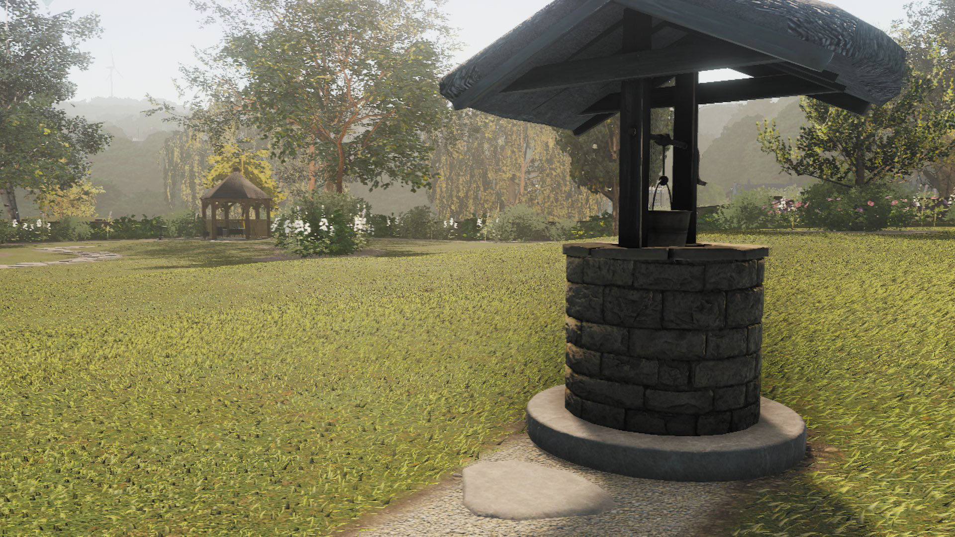 A screenshot from Lawn Mowing Simulator, showing a well at the centre of a large lawn, with a small gazebo in the distance.