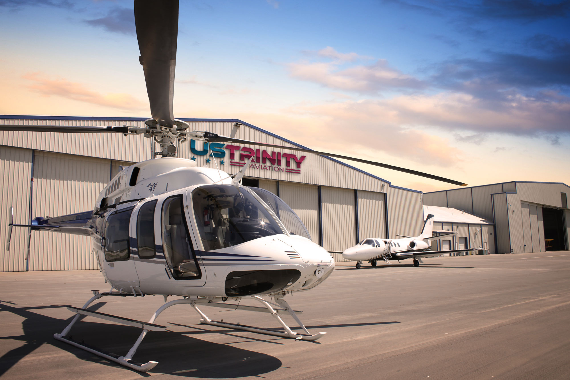 Exterior image of US Trinity Aviation Hangar with helicopter and jet