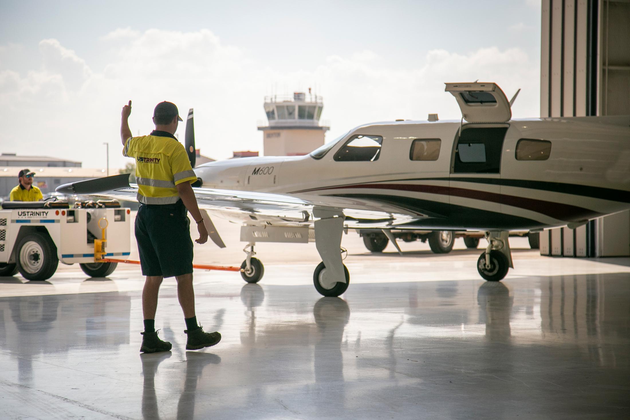 Wingwalker assisting aircraft movement