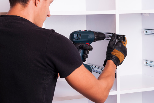 A man installing a closet system.