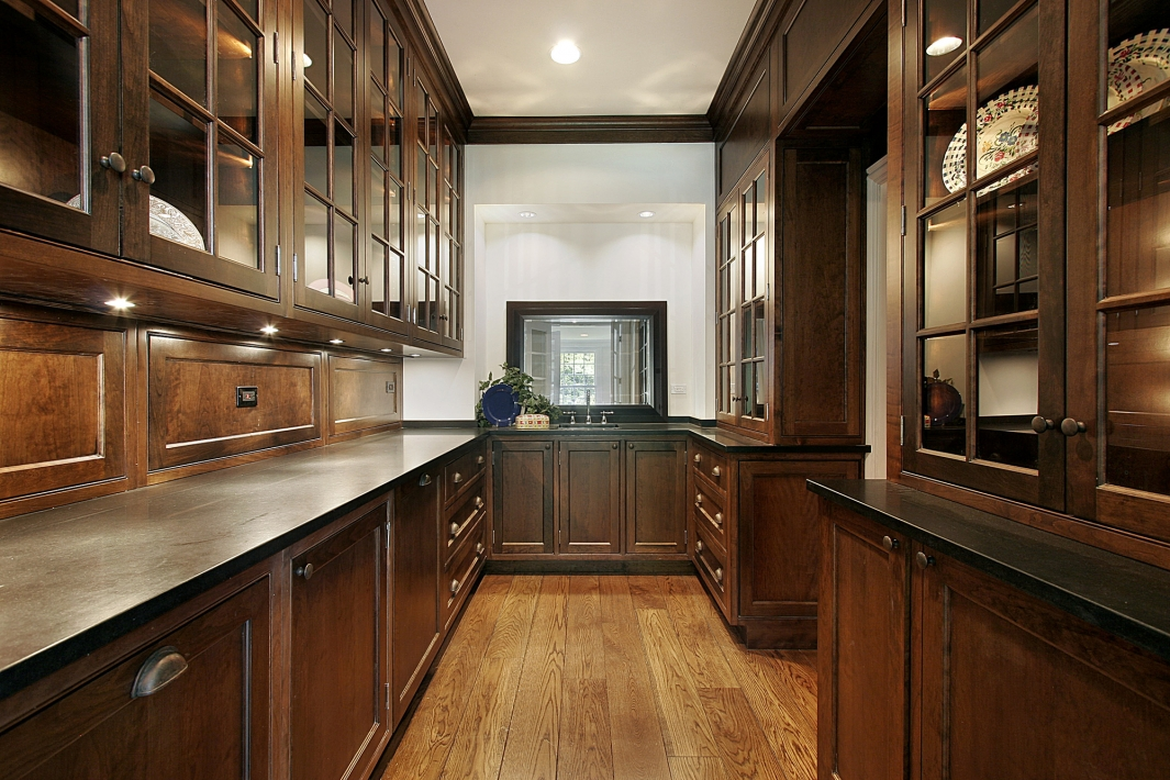 A beautiful custom kitchen pantry with dark wood finish.