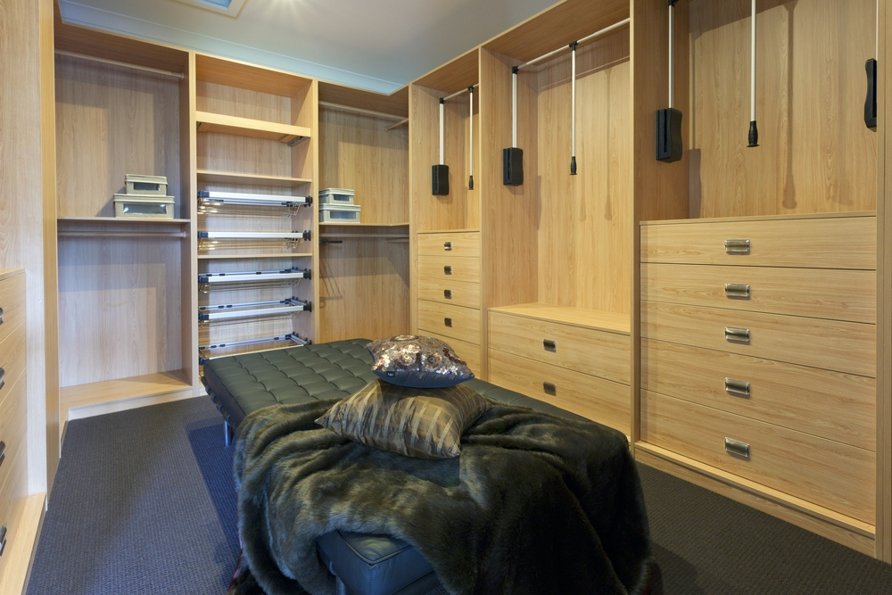 A custom walk-in closet with light maple finish and seating area in the center.